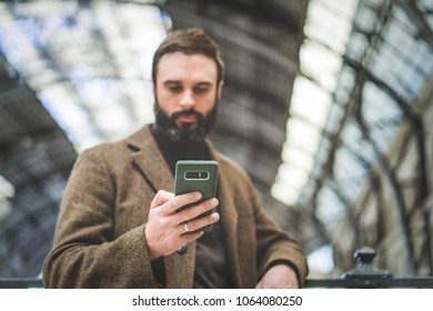 Attractive businessman sending message on his mobile phone.Casual professional entrepreneur using smartphone at hall of train station