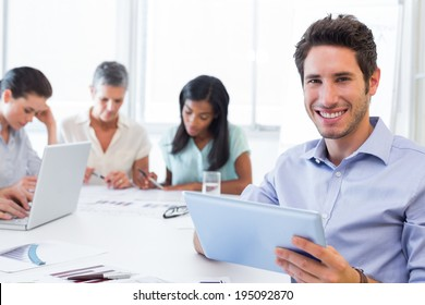 Attractive businessman smiling at the camera while using a tablet device in the office with coworkers behind