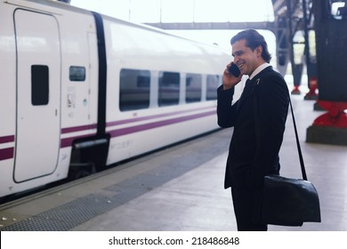 Attractive businessman stand in train station and waiting for the train, handsome man talking on mobile phone standing in railway station, rich man in suit going to work wait for the train in platform