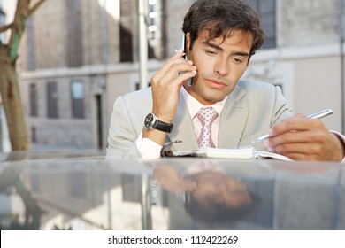 Attractive businessman using a cell phone and taking notes while leaning on a car in the city.