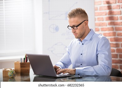 Attractive Businessman Using Laptop Over The Desk In Office