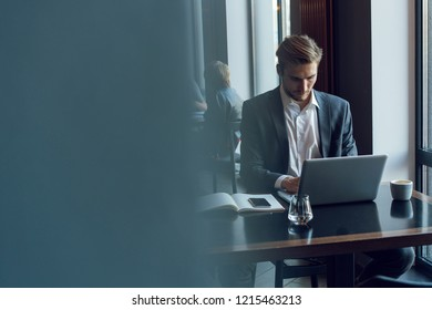 Attractive businessman using a laptop and smiling while working in cafe.