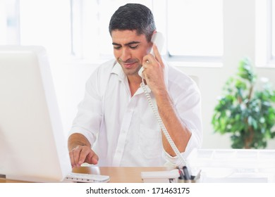 Attractive businessman using phone and computer at desk in office
