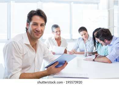 Attractive businessman using tablet device at work while smiling at the camera