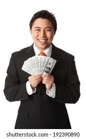 Attractive businessman wearing a suit and tie, holding a fan of hundred dollar bills. White background.