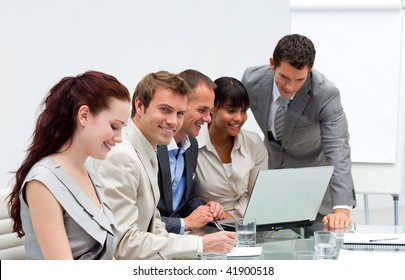 Attractive businessman working with his team with a laptop