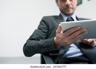 Attractive businessman working with tablet and touching digital display.