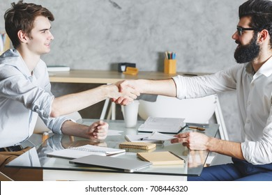 Attractive businessmen shaking hands while sitting at office desk. Teamwork, deal and cooperation concept