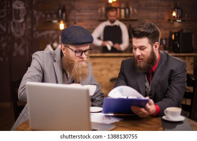 Attractive businessmen talking about finances during their meeting in a coffeee shop.