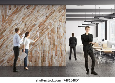 Attractive businessmen and woman in modern coworking office interior with copy space on wooden wall. Meeting concept. 3D Rendering