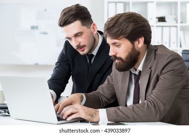 Attractive businesspeople with beards sitting at office desk and discussing business project on laptop