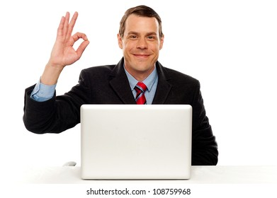 Attractive businessperson showing okay gesture to camera while working on laptop