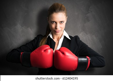 attractive businesswoman with boxing gloves ready for a fight