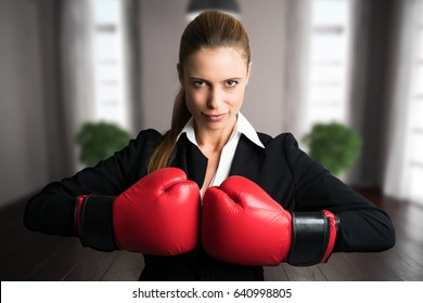 attractive businesswoman with boxing gloves ready for a fight in front of an apartment