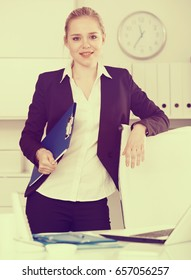 Attractive businesswoman with clipboard in hands ready to work in office
