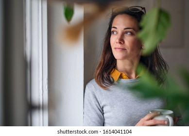 Attractive businesswoman with coffee standing indoors in office, resting.