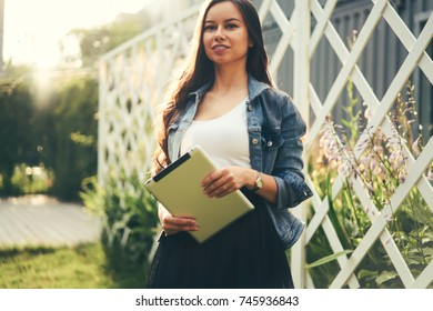 Attractive businesswoman dressed in stylish denim jacket holding modern tablet in hands standing outdoors in sunshine.Beautiful female with gorgeous brunette hair looking away while walking in street