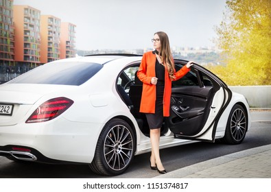 Attractive businesswoman with glasses and red coat gets out of the white Mercedes S-Class car, modern city background with rear view of the car
