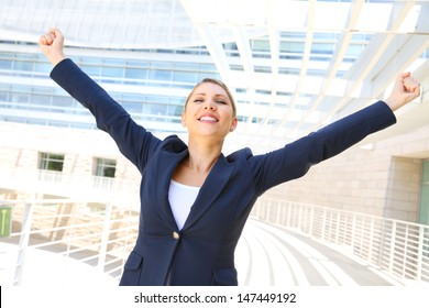 attractive businesswoman with her arms raised