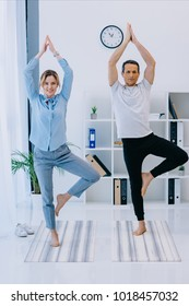 attractive businesswoman with her trainer practicing yoga in tree pose at office
