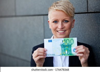 Attractive businesswoman holding 100 euro
