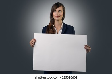 Attractive businesswoman holding a blank white sign board in her hands in front of her chest with copy space for your text or advertising, over a grey background