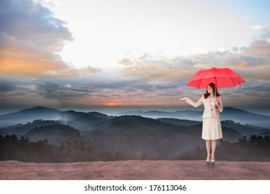 Attractive businesswoman holding red umbrella against epic mountain scenery