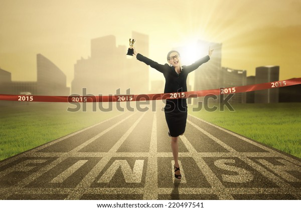 Attractive businesswoman holding a trophy in the finish line with number 2015
