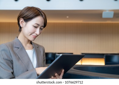 Attractive businesswoman looking tablet PC.