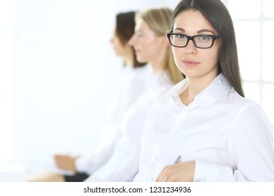 Attractive businesswoman at meeting or conference against the background of colleagues. Group of business people at work. Portrait of lawyer or secretary