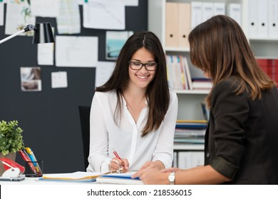 Attractive businesswoman in a meeting in the office with a female colleague smiling as she writes something in a file