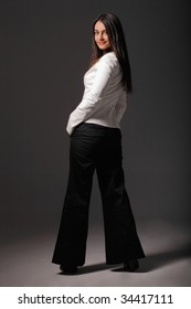 Attractive businesswoman posing with her hands in one's pockets posing