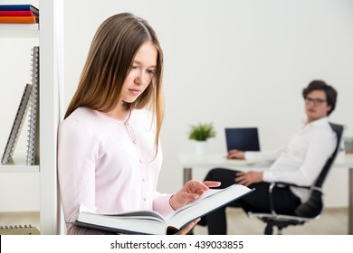Attractive businesswoman reading book in office and blurry businessman in the background looking at her