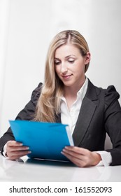 Attractive businesswoman reading her notes seated at a table holding a blue folder over a white background