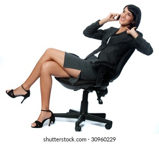 An attractive businesswoman sitting down and using a phone on white background
