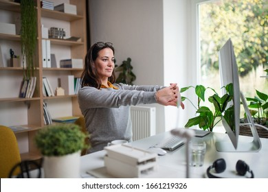 Attractive businesswoman sitting indoors in office, stretching.