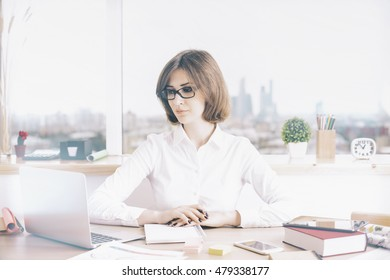 Attractive businesswoman sitting at office desktop with laptop and other items. Window with city view in the background