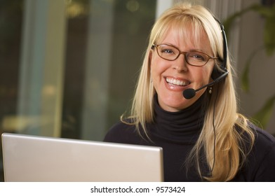 Attractive businesswoman smiles as she talks on her phone headset.