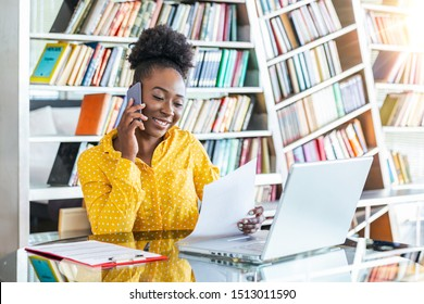 Attractive businesswoman, speaking on the phone, African American woman at training seminar, female business leader going true paperwork at her office