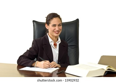 Attractive businesswoman in a suit, smiling while at her desk writing. Isolated against white