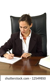 Attractive businesswoman in a suit while at her desk writing isolated against white.
