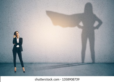 Attractive businesswoman with superhero shadow on concrete wall background. Confidence and success concept