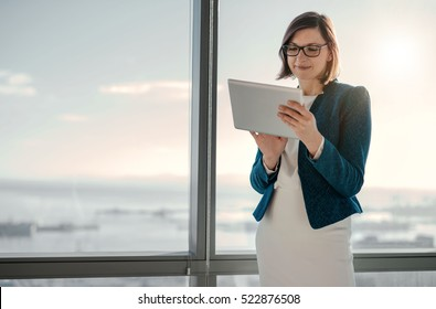 Attractive businesswoman using a digital tablet while standing in front of windows in an office building overlooking the city