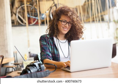 Attractive businesswoman using laptop at city cafe. Toothy smile.