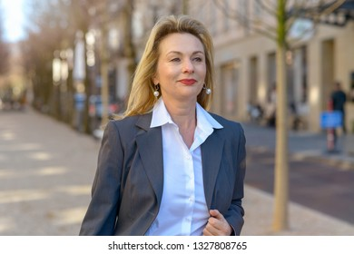 Attractive businesswoman walking confidently down a town street holding the lapel of her jacket with a smile