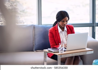 Attractive businesswoman wearing a red blazer busy working on her notebook computer in a business lounge, seated on a blue and grey couch with foreground blur visible in the image.