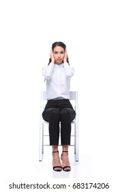 attractive businesswoman in white shirt closing ears with hands while sitting on chair, isolated on white