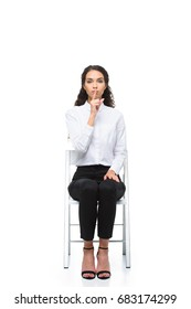 attractive businesswoman in white shirt showing silence symbol while sitting on chair, isolated on white