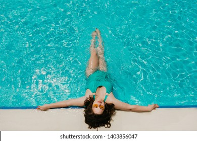 Attractive busty curvy woman in yellow sunglasses and a blue swimsuit resting by the pool. Stylish accessories, fringe, fashion for plus size. Bodypositive, natural real beauty, resort, summer