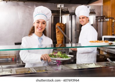 Attractive cafe staff posing at kebab counter and smiling